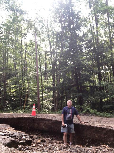 man waist deep in damaged ditch